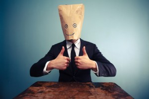 Businessman with bag over head giving thumbs up